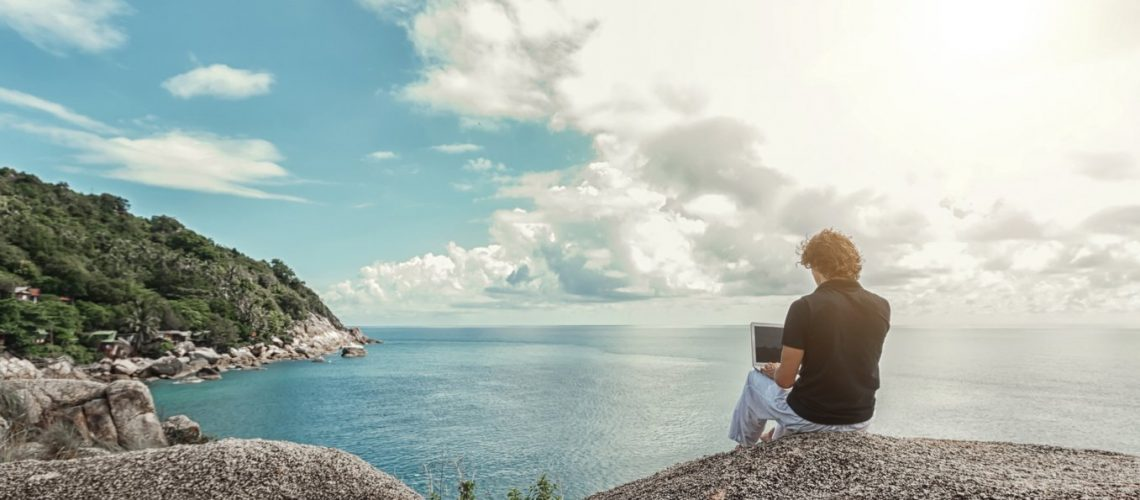 Young man, the freelancer sits on a high cliff over the sea and works remotely