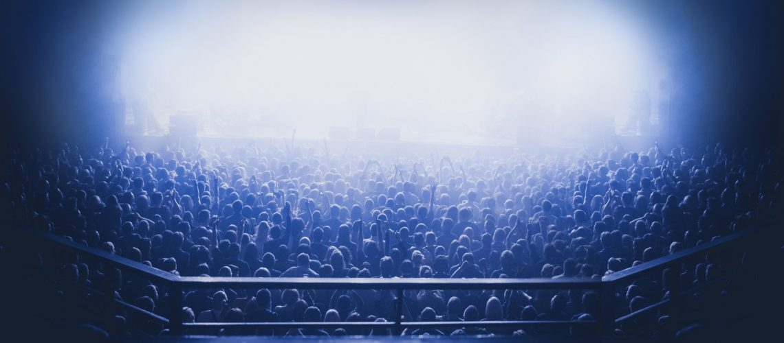 silhouettes of concert crowd in front of bright stage lights. Dark background, smoke, concert  spotlights. view from above